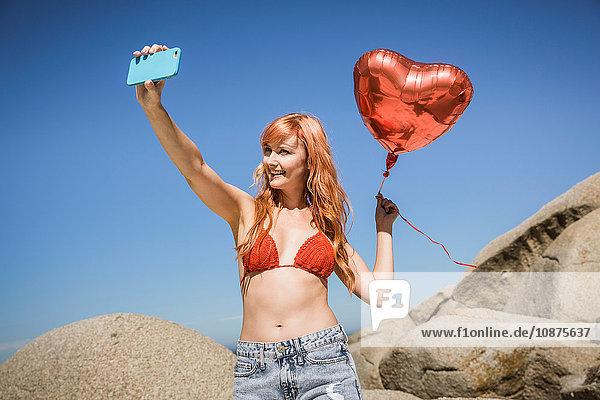 Junge Frau hält herzförmigen Luftballon in der Hand und fotografiert sich selbst mit einem Smartphone