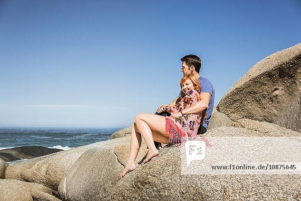 Ehepaar sitzt zusammen auf Felsen und schaut auf den Ozean