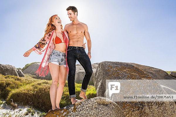Paar im Freien  auf Felsen stehend  lachend
