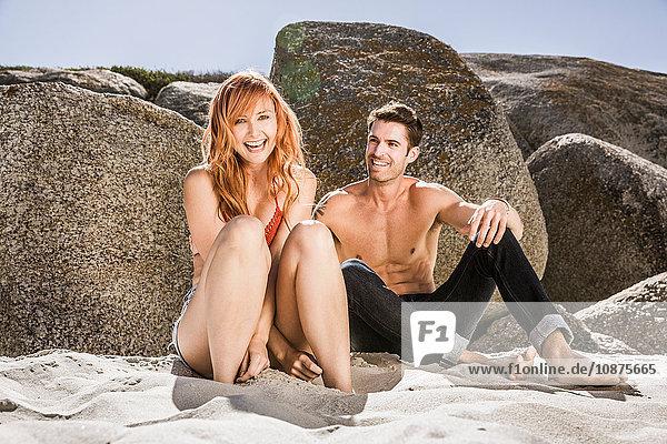 Paar sitzt am Strand  gegen Felsen  lacht