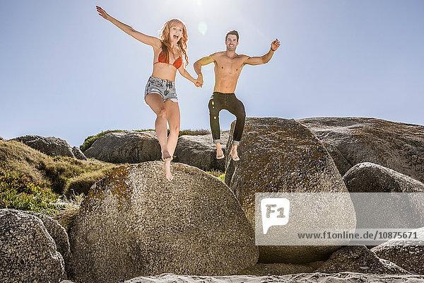 Paar im Freien  Händchen haltend  vom Fels auf Sand springend
