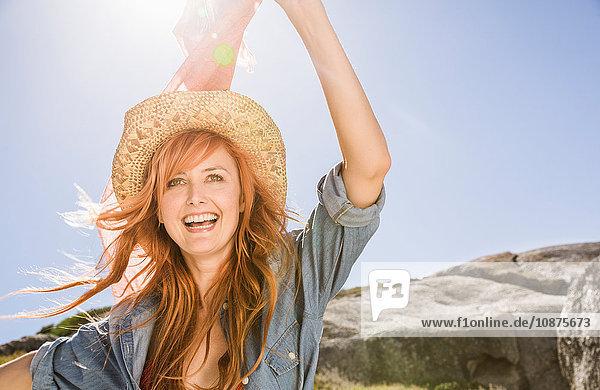 Bildnis einer jungen Frau mit roten Haaren  im Freien  Strohhut tragend
