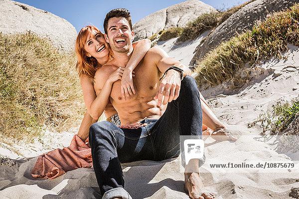 Ein Paar sitzt am Strand  neben Felsen  umarmt sich  lacht