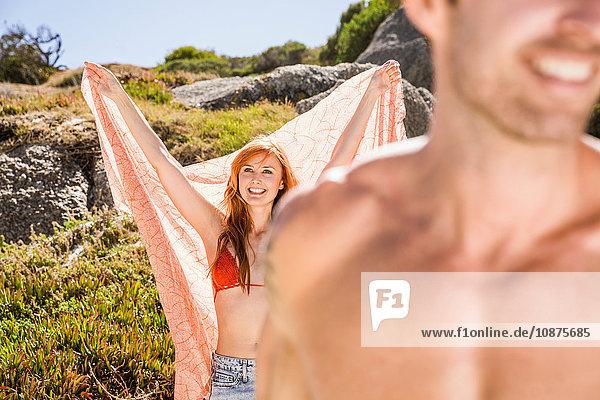Paar am Strand  Blick auf Frau  die ein großes Tuch hinter sich hält und lächelt