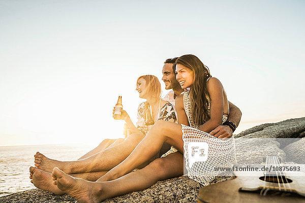 Drei mittelgroße erwachsene Freunde sitzen bei Sonnenuntergang mit Flaschenbier am Strand  Kapstadt  Südafrika