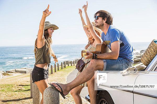 Mittlere erwachsene Freunde sitzen im Auto  spielen Gitarre und tanzen an der Küste  Kapstadt  Südafrika