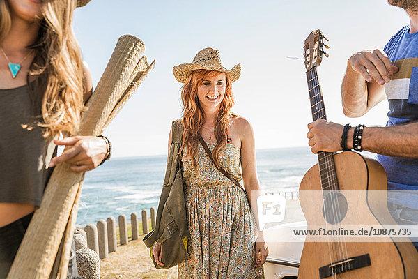 Drei mittelgroße erwachsene Freunde mit Akustikgitarre und Matte auf der Küstenstraße  Kapstadt  Südafrika