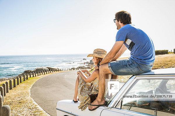 Mittelgroßes erwachsenes Paar  das vom Autodach auf der Küstenstraße hinaussieht  Kapstadt  Südafrika