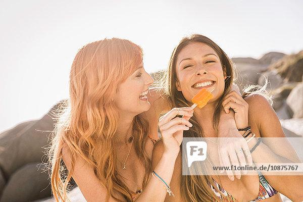 Mittlere erwachsene Freundinnen essen Eis am Strand  Kapstadt  Südafrika