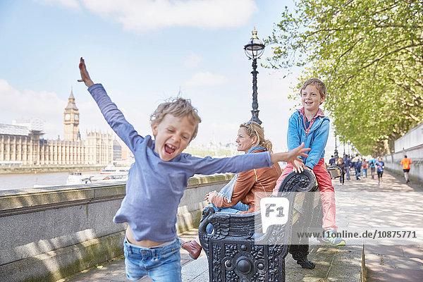 Mutter und Söhne auf Bank an der Themse