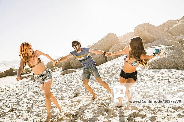 Drei erwachsene Freunde halten am Strand Händchen  Kapstadt  Südafrika