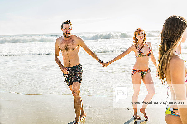 Mid adult couple wearing bikini and swimming shorts holding hands at beach  Cape Town  South Africa