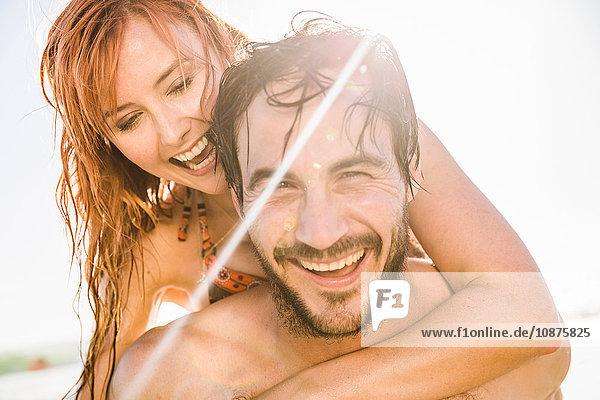 Porträt eines mittelgroßen Mannes  der seine Freundin huckepack am sonnenbeschienenen Strand gibt  Kapstadt  Südafrika