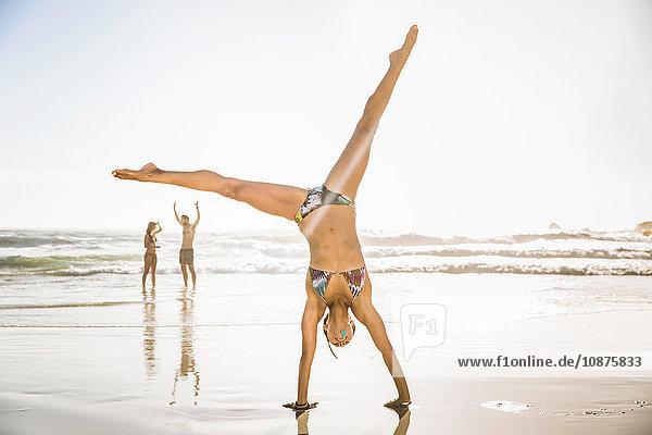 Mid adult woman wearing bikini cartwheeling on beach  Cape Town  South Africa