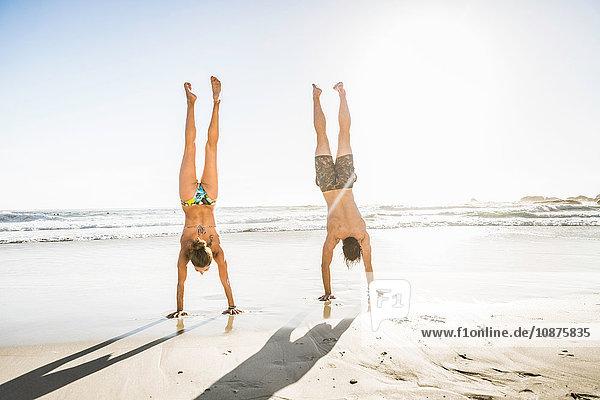 Mittelerwachsenes Paar macht Handstand am Strand  Kapstadt  Südafrika