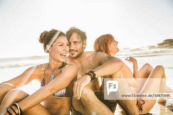 Drei mittelgroße erwachsene Freunde sitzen am Strand  Kapstadt  Südafrika