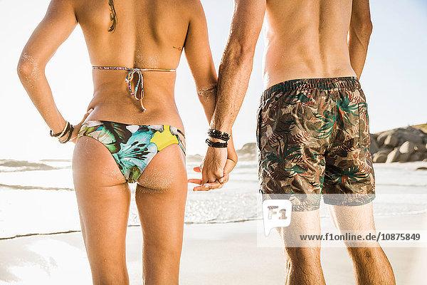 Rückansicht eines Paares im mittleren Erwachsenenalter in Shorts und Bikini am Strand  Kapstadt  Südafrika