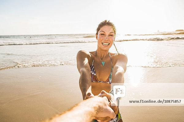 Mittlere erwachsene Frau im Bikini  die ihren Freund am Strand an der Hand hält  Kapstadt  Südafrika