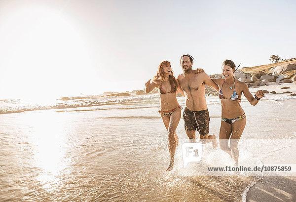 Drei mittlere erwachsene Freunde laufen im Meer  Kapstadt  Südafrika