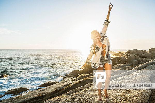 Mittlere erwachsene Frau tanzt am sonnenbeschienenen Strand  Kapstadt  Südafrika