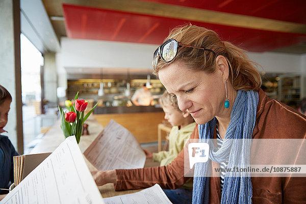 Mutter und Sohn im Café beim Blick auf die Speisekarte