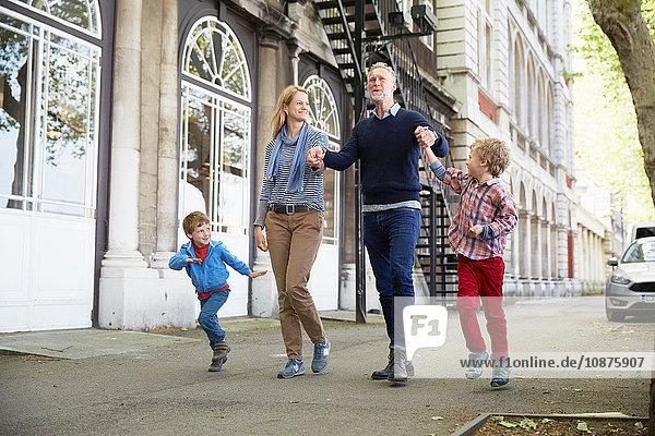 Familie geht auf der Straße und hält sich an den Händen