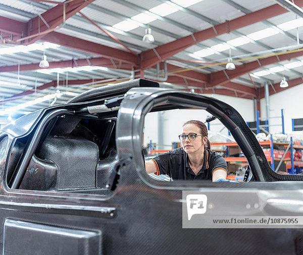Ingenieurin inspiziert Kohlefaser-Karosserie in Rennwagenfabrik