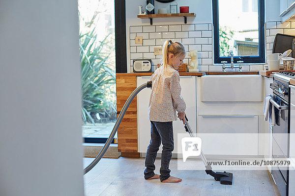 Mädchen beim Staubsaugen des Küchenbodens