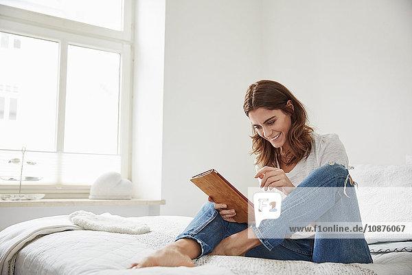Schöne junge Frau sitzt auf Bett und benutzt digitales Tablett