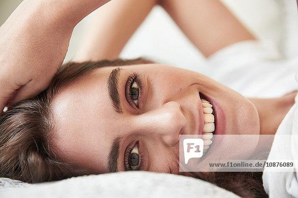 Nahaufnahme eines Porträts einer schönen jungen Frau  die auf einem Bett liegt