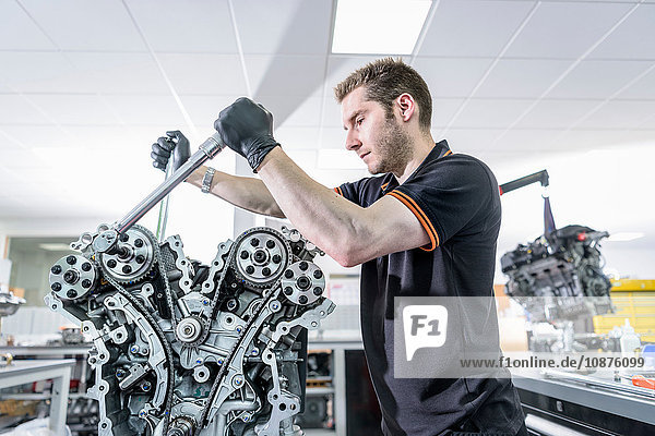 Engineer working on engine in racing car factory
