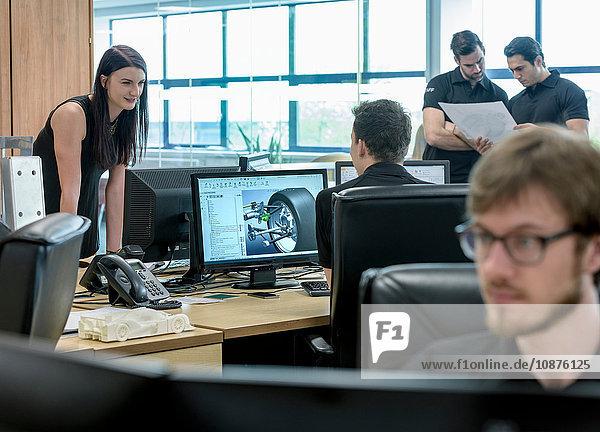 Ingenieure arbeiten in Rennwagenfabrik mit CAD-Konstruktionsbildern