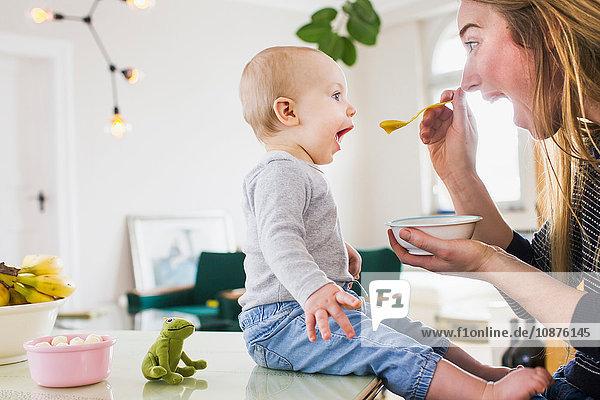 Mädchen ahmt Mutter beim Essen am Küchentisch nach Mädchen ahmt Mutter beim Essen am Küchentisch nach