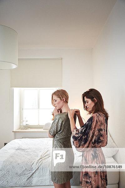 Zwei junge Frauen  die sich im Schlafzimmer mit Reißverschlusskleidern fertig machen