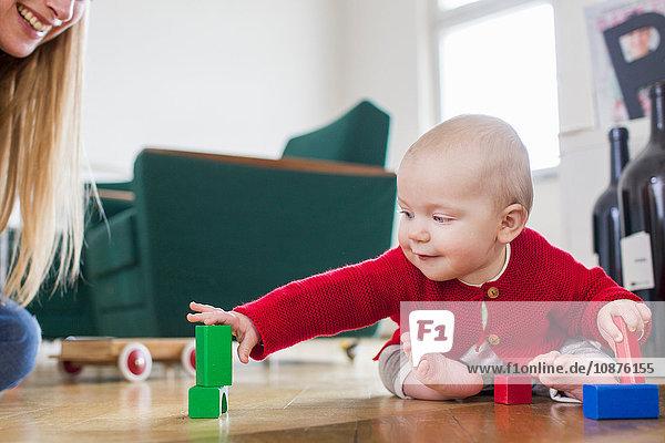 Kleines Mädchen spielt mit Bauklötzen auf dem Wohnzimmerboden