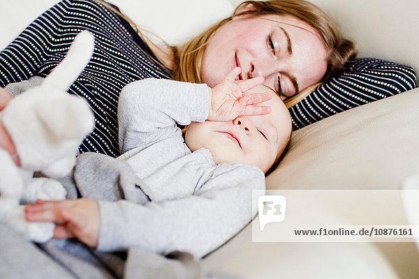 Müdes Mädchen und Mutter auf dem Sofa liegend