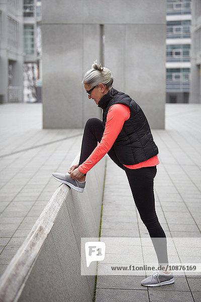 Ausbildung einer reifen Frau in der Stadt  Schnürsenkel der Trainerin binden