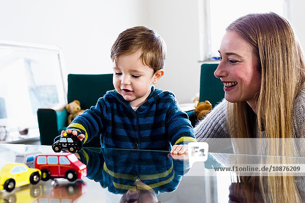 Mid adult woman and baby son playing with toy cars on table