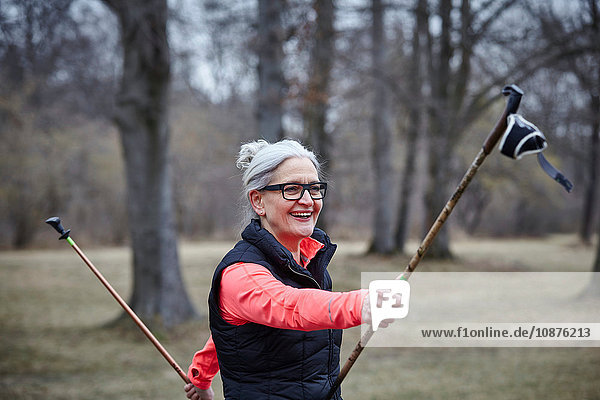 Mature female training in park  exercising with nordic walking poles