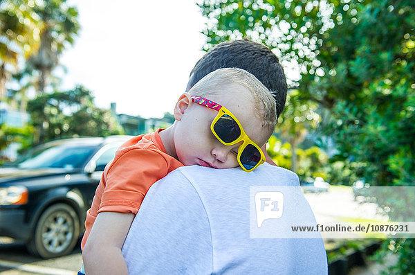 Father carrying sleeping boy wearing yellow sunglasses