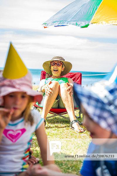 Kinder spielen auf einer Party vor einer älteren Frau auf einem Liegestuhl an der Küste  Waiheke Island  Neuseeland