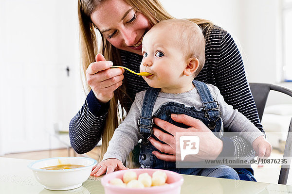 Woman feeding baby daughter at table