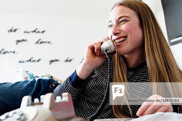 Mittlere erwachsene Frau  die im Bett liegt und über Festnetztelefon spricht