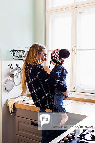 Mid adult woman carrying baby son in kitchen