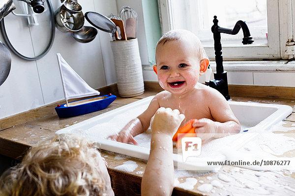 Junge spielt mit kleinem Bruder beim Baden in der Küchenspüle