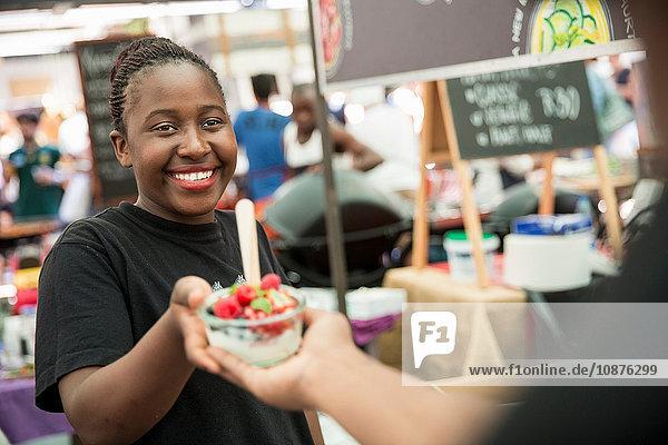 Weiblicher Standinhaber serviert Fruchtsalatbeeren an einem Genossenschaftsstand auf dem Lebensmittelmarkt