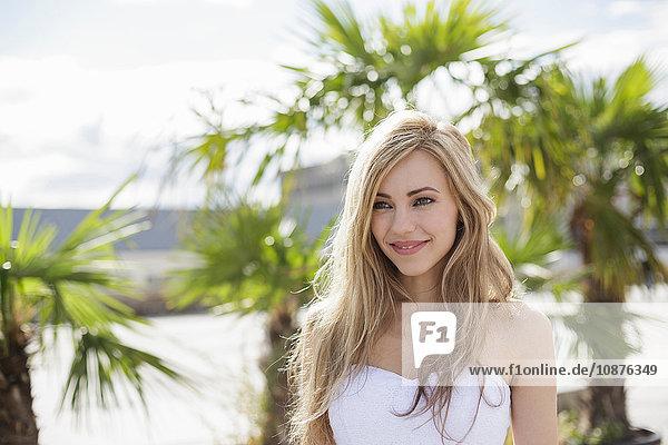 Schöne langhaarige blonde junge Frau in der Stadt