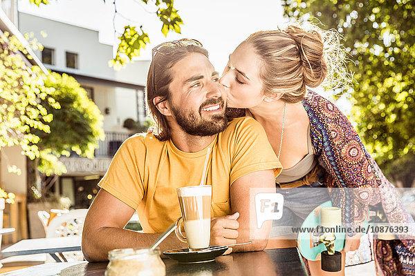 Junge Frau küsst ihren Freund auf die Wange im Straßencafé  Franschhoek  Südafrika