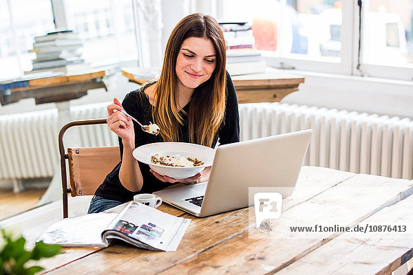 Junge Frau in Stadtwohnung isst Müslifrühstück und liest dabei am Laptop