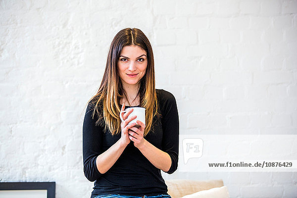 Portrait of beautiful young woman in apartment holding coffee mug